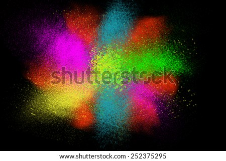 Freeze motion of colorful powder paint exploding isolated on black dark background. Abstract design of color dust cloud. Particles explosion screen saver, wallpaper brush  - stock photo