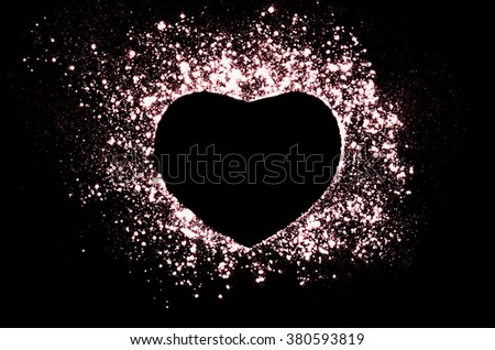 Freeze motion of heart shaped red powder on black, dark background. Abstract design of dust cloud. Particles explosion screen saver, wallpaper with copy space. Love, passion, feelings concept. - stock photo