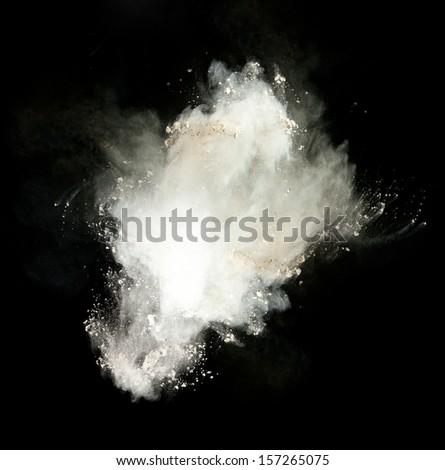 Freeze motion of white dust explosion isolated on black background - stock photo