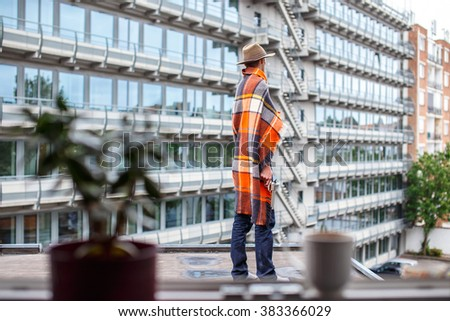 Freezed man covered with blanket on the roof. - stock photo