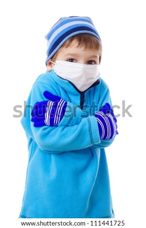 Freezing boy in winter clothes and medical mask, isolated on white - stock photo