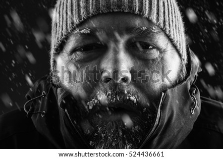 Freezing cold man standing in a snow storm blizzard trying to keep warm. Wearing a beanie hat and winter coat with frost and ice on his beard and eyebrows staring at the camera. Black and white.