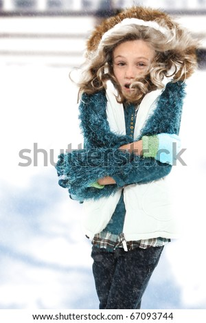Freezing cold seven year old girl standing in snow storm without coat. - stock photo