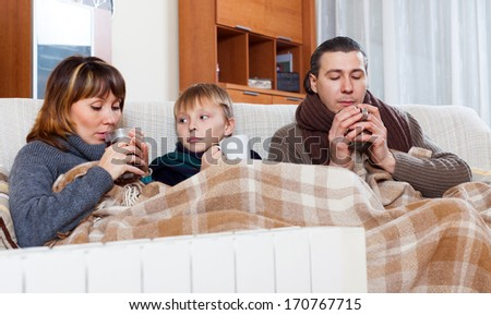 freezing family of three with cups of tea warming near warm radiator in home - stock photo