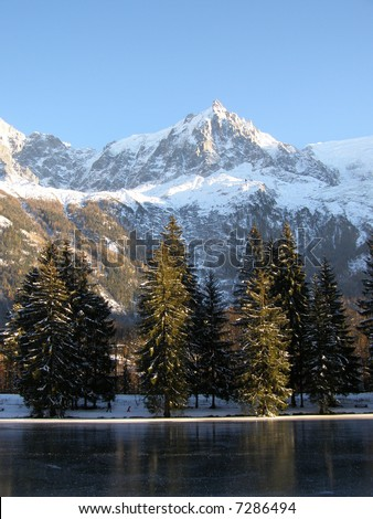 Freezing lake in front of Aiguille du Midi and firs to Chamonix (France) at sunset