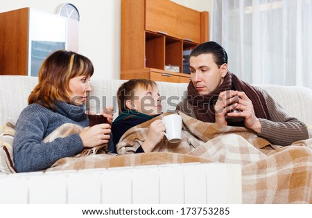 freezing parents and teenage son warming near warm heater in home - stock photo