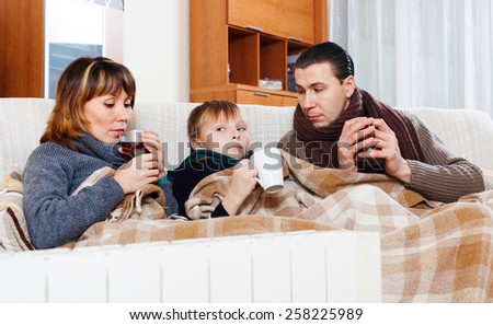freezing parents and teenage son with cups of tea warming near warm calorifer in home - stock photo