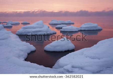 Freezing sea at sunset; fresh white snow at ice-covered stones and vapor hiding horizon. Photographed at Baltic sea, Estonia, January 10, 2016.