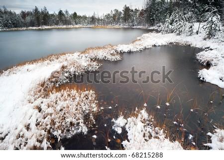 Freezing taiga lake with the various invoice of ice, Siberia - stock photo