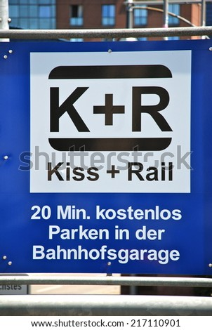 FREIBURG IM BREISGAU, GERMANY - JULY 9, 2011: Signpost at the central railway station of Freiburg in Breisgau, Germany, 20 minutes free parking for kissing before leaving apart. - stock photo