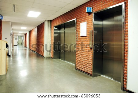Freight and regular steel door elevators with signs in an empty hallway of modern building. Can be office, school, hospital. - stock photo