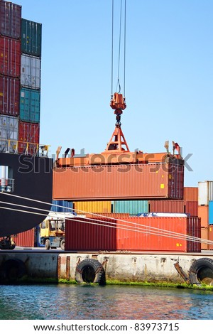 Freight container on lift in sea port - stock photo