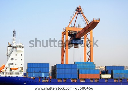 Freight containers on board under crane bridge - stock photo