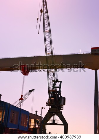 Freight shipping or freight transportation. Hamburg Harbor with harbor cranes in the sunset.