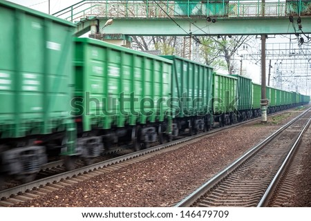 Freight train at fast speed in the movement under the bridge for pedestrians - stock photo