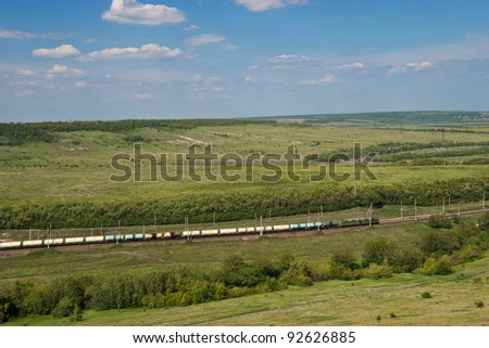 Freight Train Going by Railway Against Summer Landscape - stock photo