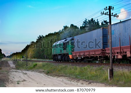 Freight train hauled by the diesel locomotive passing the forest - stock photo