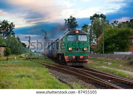 Freight train hauled by the diesel locomotive passing the station - stock photo