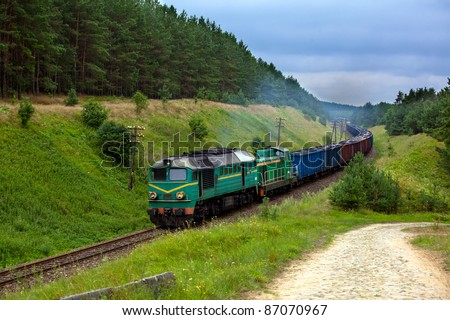 Freight train hauled by the diesel locomotives passing the forest - stock photo
