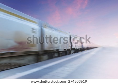 Freight train in blurred motion on purple and blue evening sky - stock photo
