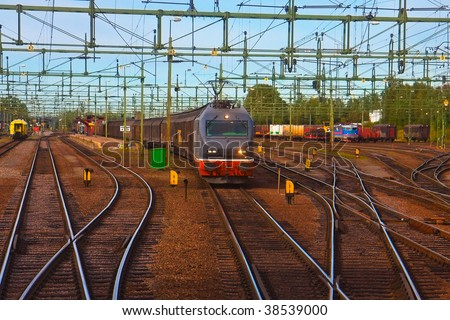 Freight train passing railway station - stock photo