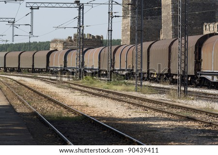 Freight train passing railway station - stock photo
