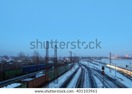 Freight trains with carriages stand on railways at snowy winter evening - stock photo