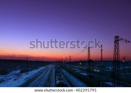 Freight trains with carriages stand on railways at winter during sunset - stock photo