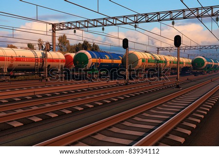 Freight trains with fuel tank cars at the railroad station in sunset - stock photo