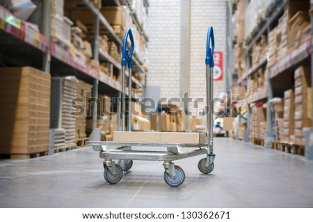 Freight trolley with box on it on modern warehouse - stock photo