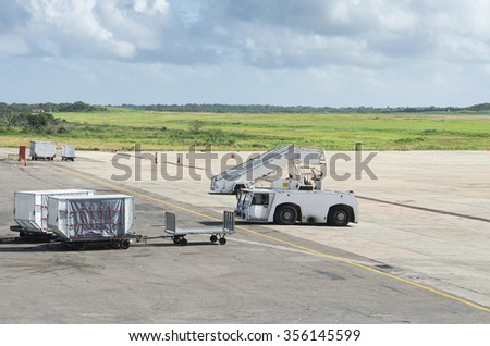 Freight trolleys with loaded baggage on the runway tarmac - stock photo