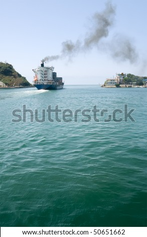 Freighter navigate on ocean with blue sky and green water in Kaohsiung, Taiwan. - stock photo