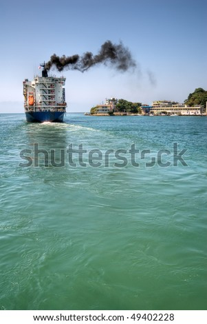 Freighter navigate the port with black smoke of sea in Kaohsiung, Taiwan. - stock photo