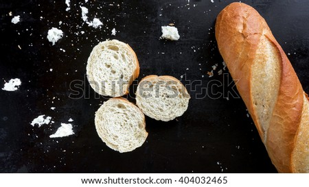 French baguette and crumbs on dark background - stock photo
