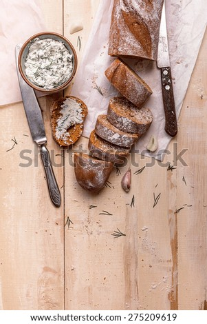 French baguette cut into pieces, garlic, ricotta cottage cheese on a rustic wooden board with knife over light old painted background. Top view - stock photo