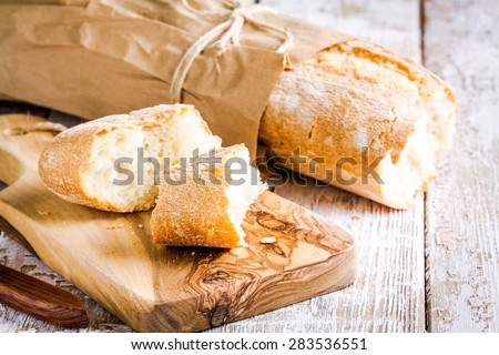 French Baguette on cutting board on white rustic table - stock photo