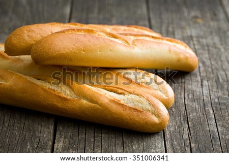 french baguettes on old wooden background - stock photo