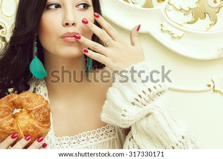 French bakery concept. Portrait of a young beautiful woman eating her croissant and getting pleasure in a vintage bedroom. Close up. Perfect skin, make up, manicure. Indoor shot