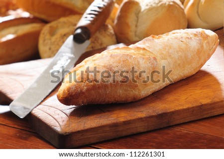 French bread baguette on vintage wooden bread board and knife. Selective focus with background of assorted bread rolls. - stock photo