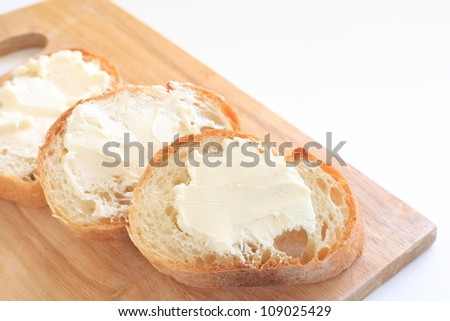French bread, Baguette sliced on chopping board - stock photo