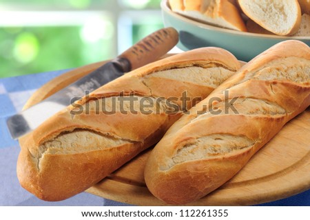 French bread baguettes on bread board and bread-knife - stock photo