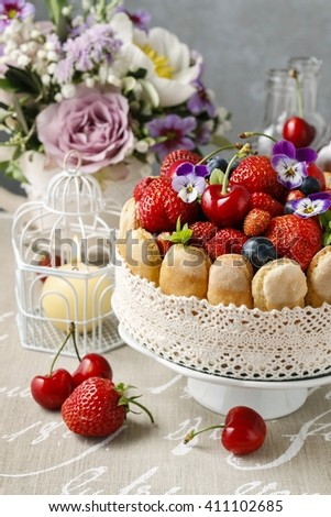 French charlotte cake with summer fruits decorated with pansy flowers. - stock photo