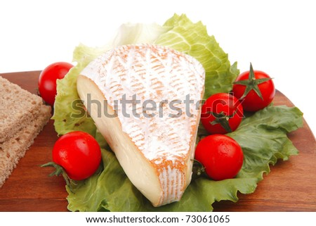french cheese and tomatoes on wooden plate