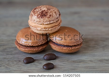 French Chocolate & Coffee Macaroons And Coffee Beans, Tasty Gourmet Meringue Cookie Sandwich Cake on Vintage Wood Background