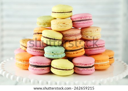French colorful macarons on cake stand on white wooden background - stock photo