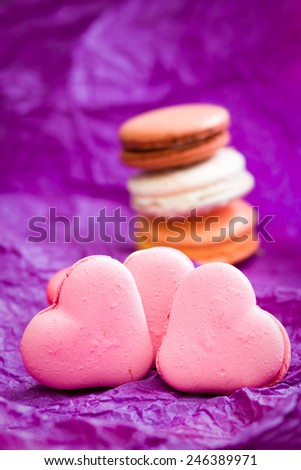 French colorful macarons with hearts on violet background  - stock photo