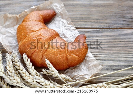 French croissant on paper, tasty food - stock photo
