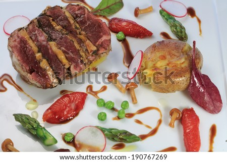 French cuisine: Beefsteak and foie gras dish served with asparagus, wild mushrooms and salad leaves - stock photo