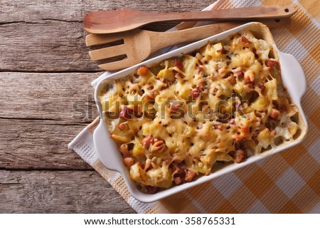 French cuisine: tartiflette potatoes with bacon and cheese close up in baking dish. horizontal top view - stock photo