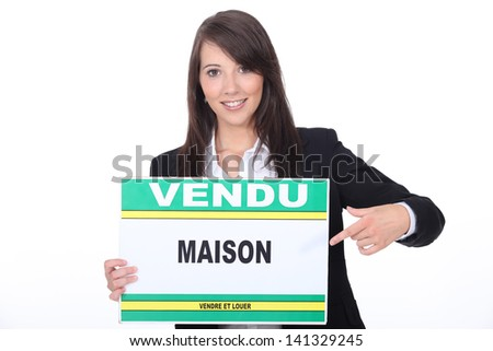 French Estate Agent with a 'Vendu' sign - stock photo